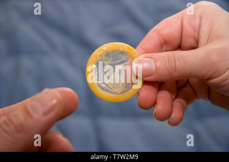 Woman's hand giving condom to man's hand. - Stock Image