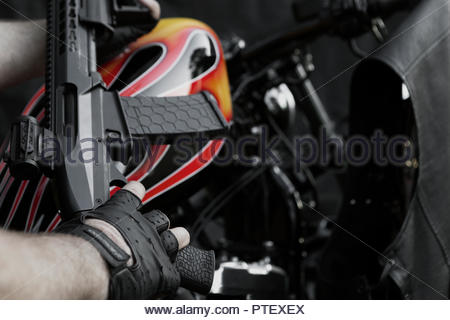 Modern Weapon Held Over a Custom Flame Painted Bikie Style Motorcycle - Leather Vest - ii - Stock Image