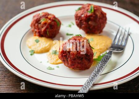 Beet Dumplings (Knödel) with Vegan Cheese Sauce - Stock Image
