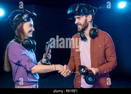 Man and woman shaking hands before the game in virtual reality standing together in the playing club - Stock Image