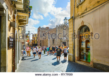 Tourists sightseeing on the main street, Corso Umberto, in the Mediterranean resort town of Taormina Italy on the island of Sicily - Stock Image