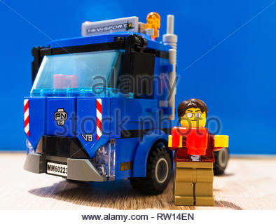 Poznan, Poland - February 27, 2019: Lego driver figure standing with a coffee next to a parked truck having a work break. - Stock Image