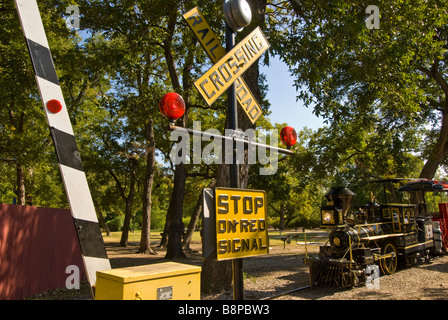 San Antonio Zoo miniature train Brackenridge Park railroad crossing with working stop gates Texas TX - Stock Image
