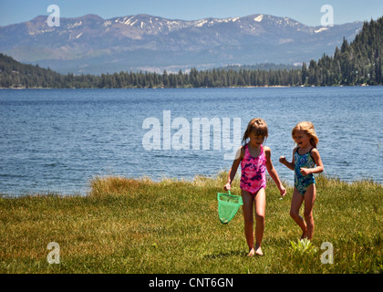 two young girls mountain lake rural scenery pond woods environment view - Stock Image