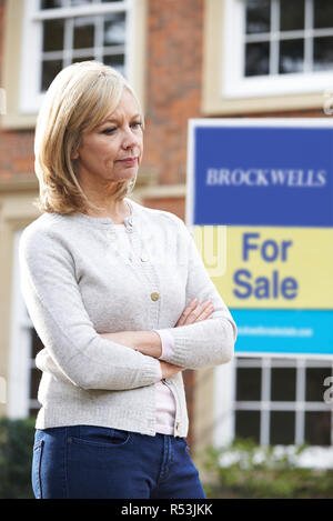 Mature Woman Forced To Sell Home Through Financial Problems - Stock Image