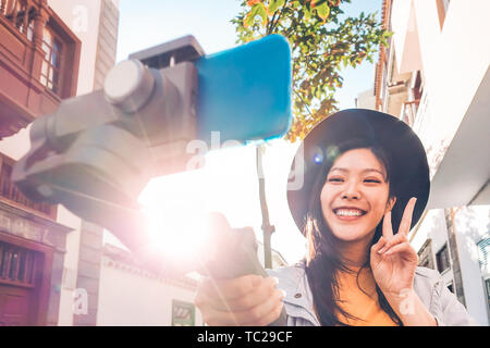 Asian woman making video blog with smartphone gimbal outdoor - Happy Asiatic influencer having fun with new technology trends for social media - Stock Image