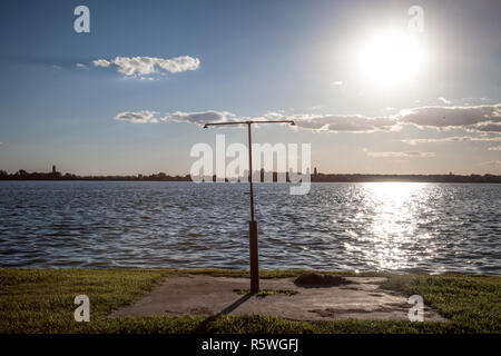Rusty shower on a beach facing the Blue water of Palic Lake, in Subotica, Serbia, during a summer sunset Also known as Palicko Jezero, it is one of th - Stock Image