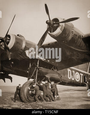 Ground crew moving a 20 ton Short Stirling, British heavy bomber of the Second World War. The first four-engined bomber to be introduced into Royal Air Force squadron service in early 1941. The Stirling was relegated to second line duties from late 1943, due to the increasing availability of the more capable Handley Page Halifax and Avro Lancaster, which took over the strategic bombing of Germany. - Stock Image