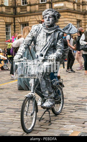 Edinburgh, Scotland, UK. 14th August 2018. Edinburgh Fringe Festival street performer, Royal Mile, Edinburgh, Scotland, United Kingdom. A street performer on a stationary bicycle painted white with pretend flying hair and scarf - Stock Image