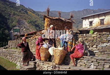 Nepalese women take a rest and adjust their loads at Navina Hotel Guest House Kimrong Khola Annapurna Circuit Nepal - Stock Image