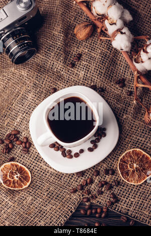 Coffee and cotton retro camera on sacking Still life with the top view - Stock Image