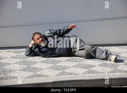 Czech Republic, Prague 16-04-2019: A homeless man lying on the floor. Mid shot - Stock Image