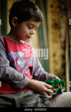 Boy aged six sucks lollipop while building toy with plastic bricks - Stock Image