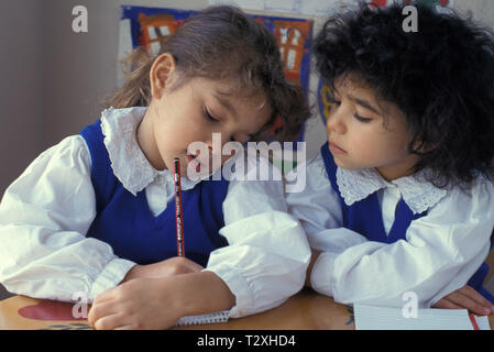 two primary schoolgirls in class one hiding her work from her peer - Stock Image