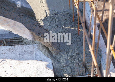 Workers pour the Foundation for the construction of a residential building using mobile concrete mixers - Stock Image