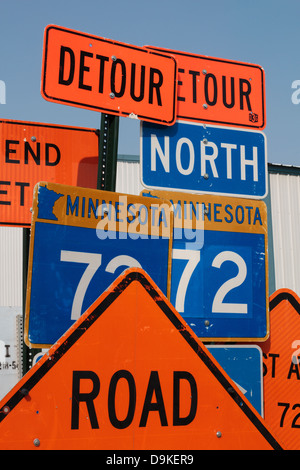 Road construction signs stacked up along the side of a street. - Stock Image