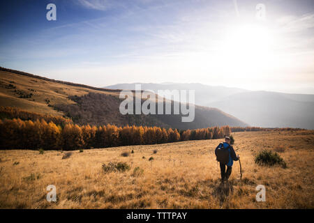 Male backpacker walking on mountain against sky - Stock Image