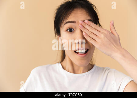 Image of attractive chinese woman wearing basic t-shirt covering her eyes and peeking isolated over beige background in studio - Stock Image