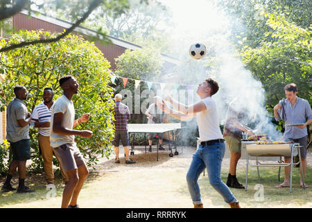 Male friends playing soccer and ping pong, enjoying backyard barbecue - Stock Image
