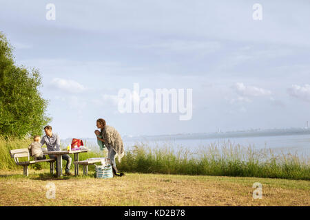 Family resting by sea - Stock Image