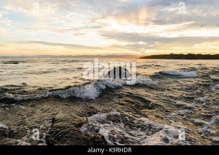Ocean sunset is a serene scenic seascape on the beach with the bright sun setting on the ocean horizon. - Stock Image