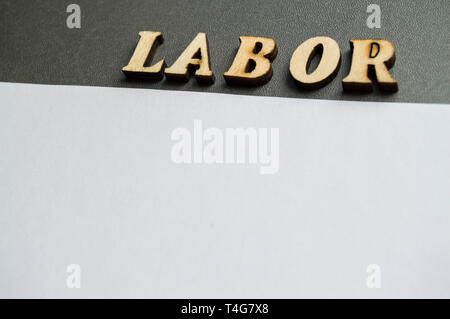 The word labor written in wooden letters to celebrate labor Day in may. Ready design layout for advertising with empty space for text. - Stock Image