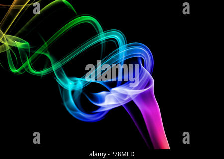 A wisp of multi-coloured smoke on a black background. - Stock Image