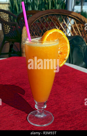 Glass of freshly squeezed orange juice with a plastic straw - Stock Image