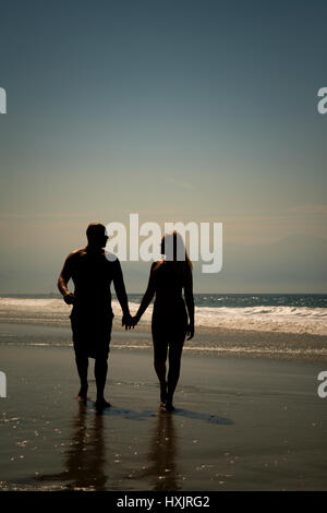 Romantic silhouette photograph of a man and a woman holding hands while walking on the beach - Stock Image