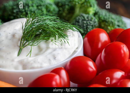 Homemade buttermilk ranch salad dressing with dill served with cherry tomatoes, baby carrots and broccoli, over a rustic wooden background. - Stock Image