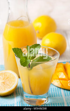 mango lemonade with a mint branch in a glass on a blue napkin, fresh mango and lemons on a white wooden background - Stock Image