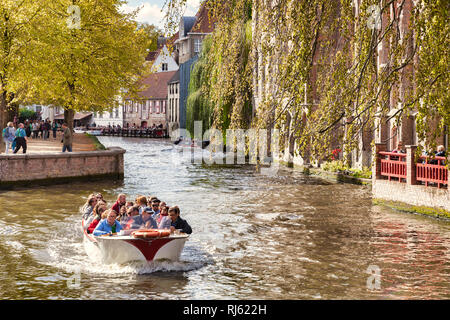 25 September 2018: Bruges, Belgium - Sightseeing boat on the Bruges canal on a sunny autumn day, trees turning to autumn colours. - Stock Image