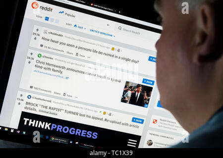 Man sitting at a computer monitor browsing through the Internet looking at the Reddit website on the World Wide Web using an Internet Browser. - Stock Image