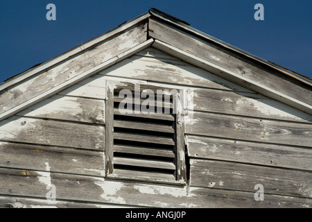 broken louver in New Orleans Lower Ninth 9th Ward  pitch roof wooden wood siding falling apart - Stock Image