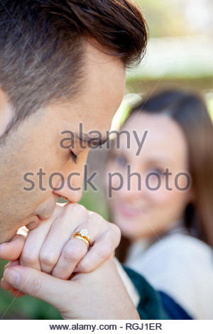 Man kisses the hand of his girlfriend who appears out of focus in the background in an outdoor location in a European city - Stock Image