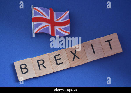 Creative Concept : British politics : 3d Union Jack flag and the word Brexit isolated on a blue background - Stock Image