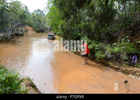 A 4x4 Nissan Patrol bogged on popular Old Telegraph Road (OTT) being rescued with a winch, Scrubby Creek, Cape York Peninsula, Queensland, Australia - Stock Image