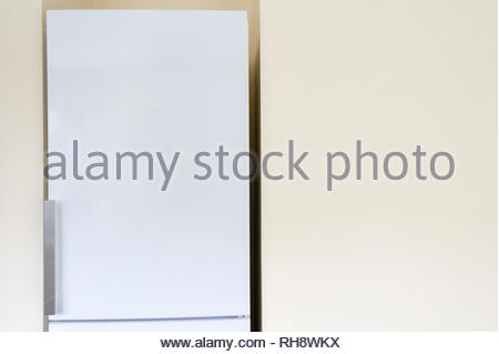 Fridge next to blank kitchen wall - Stock Image