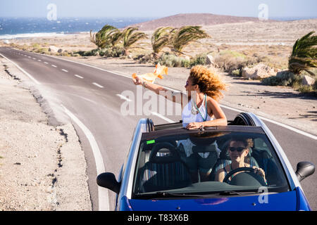 Travel and happy freedom lifestyle young people concept with couple of curly nice ladies traveling and enjoying the trip on a blue convertible car wit - Stock Image