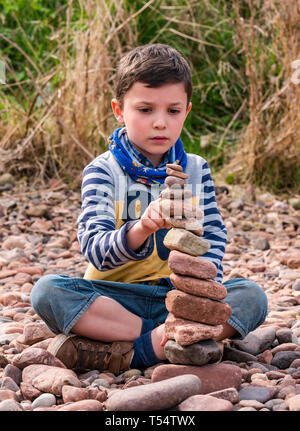 Dunbar, East Lothian, Scotland, UK. 21st Apr 2019. European stone stacking championship: Ostin balances 15 stones in the Quantity competition for children under 15 years of age –- most stones balanced vertically - at Eye Cave beach on the second day which comprises 2 competitions, a 3 hour artistic challenge and a children's competition.The overall winner receives a trip to llano Earth Art Festival & World Stone Balancing competition in Texas in 2020. Credit: Sally Anderson/Alamy Live News - Stock Image