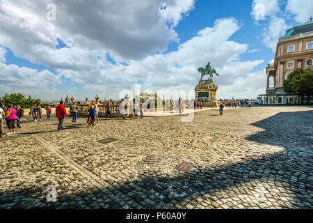 Tourists pass by the equestrian statue of Prince Savoyai Eugen on the terrace in front of the Royal Palace at Buda Castle Complex in Budapest Hungary - Stock Image