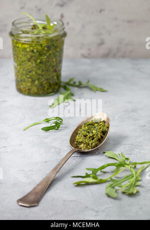 homemade arugula pesto in a glass jar on a gray concrete background. copy space - Stock Image