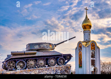 Tank momument and the orthodox church Sfantul Gheorghe in the Memorial of Glory in Suvorov Square in Tiraspol, Moldova - Stock Image