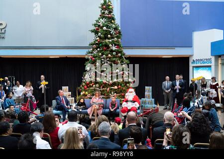 U.S. First Lady Melania Trump reads the children's book Oliver the Ornament to young patients and their families during the traditional holiday visit to Childrens National Hospital December 13, 2018 in Washington, DC. Seated next to the First Lady are patients Tearrianna Cooke-Starkey, Nathan Simm, author Todd Zimmerman and Santa Claus. - Stock Image