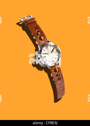 A modern watch with a leather strap on a mustard background with creative shadow. - Stock Image