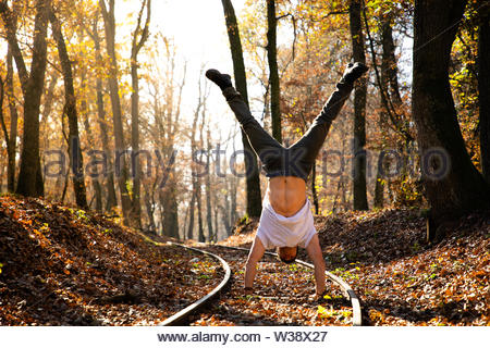 Man doing handstand on train rails with leaves on the ground during sunset - Stock Image