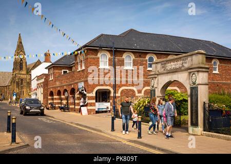 UK, England, Yorkshire, Filey, Murray Street, visitors passing War Memorial Garden - Stock Image
