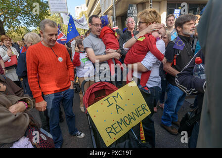 London, UK. 20th October 2018. Parents hold children with message 'I'm a Remoaner' People gather with placards, banners and flags at Hyde Park Corner for the People's Vote March calling for a vote to give the final say on the Brexit deal or failure to get a deal. They say the new evidence which has come out since the referendum makes it essential to get a new mandate from the people to leave the EU. Peter Marshall/Alamy Live News - Stock Image