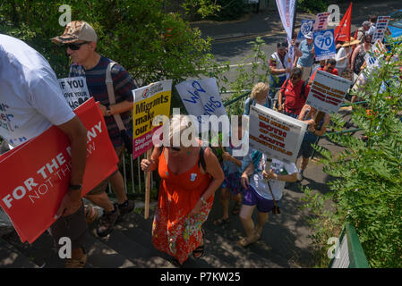 London, UK. 7th July 2018. Keep Our St Helier Hospital (KOSHH) campaigners against the closure of acute facilities at Epsom and St Helier Hospitals in south London cross a footbrindge on their march to celebrate the 70th Birthday of the NHS from Sutton to a rally in front of St Helier Hospital.  The closures are prompted by government cuts which call for huge savings by the trust, and would l Credit: Peter Marshall/Alamy Live News - Stock Image
