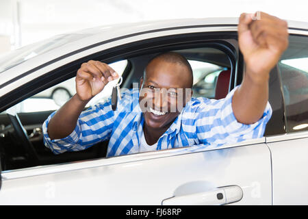 excited African man showing a car key inside his new vehicle - Stock Image